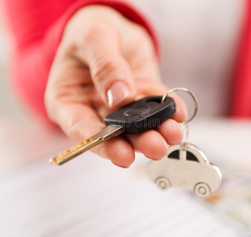 Car rent and sale. Closeup of female hand giving car key to buyer in automotive dealer's office. Auto ret, sale and inspection concept. Shallow depth of field stock images