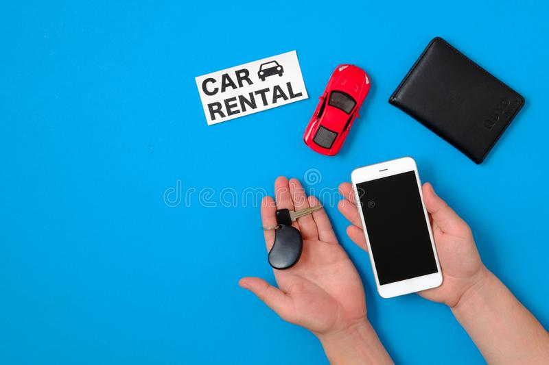 Car rental app concept. Toy car, auto drive license, human hand with smartphone and car key, text sign royalty free stock photos
