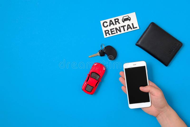 Car rental app concept. Toy car, car key, auto drive license, human hand with smartphone and text sign. `CAR RENTAL` on blue background. Flat lay composition stock photography