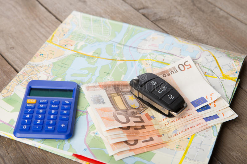 Car rental concept - car key,calc, and money on the map. Car rental concept - car key,calc and money on the road map stock images