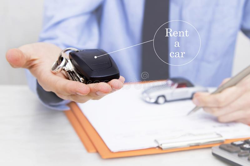 Car rental concept. Business man with car keys in office stock photos