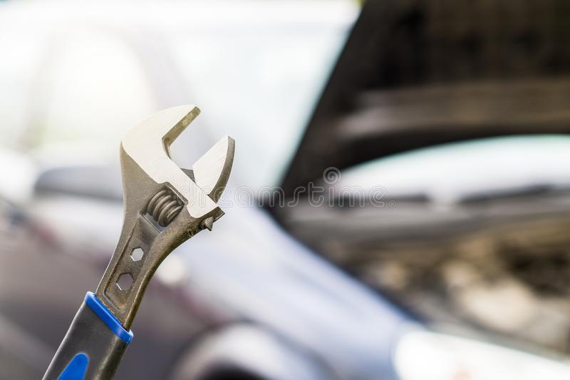 Car repair, maintenance and vehicle inspection concept. Wrench and a car with under the hood and engine view. Selective focus to fixing tool royalty free stock images