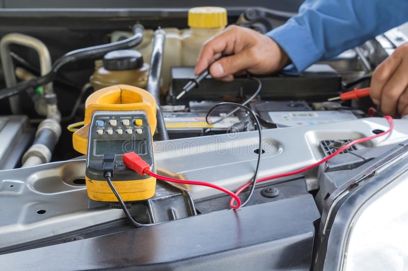 Car repair service, Auto mechanic checking a car battery level royalty free stock photo