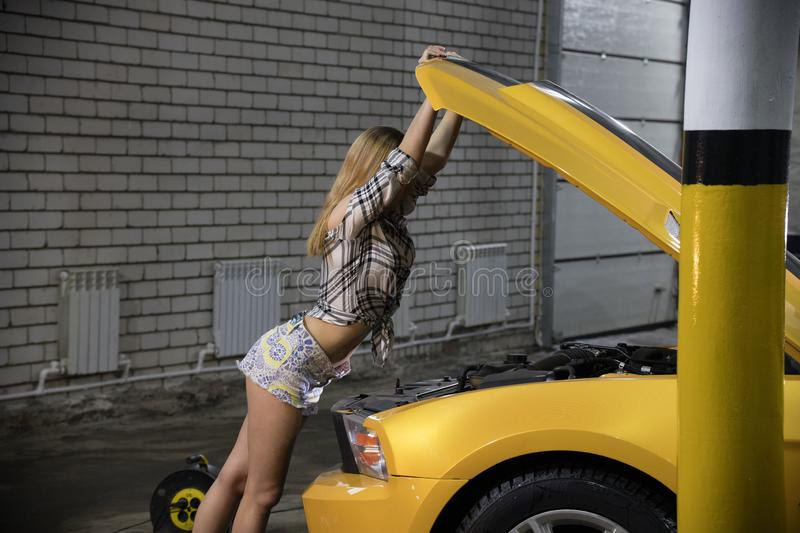 Car repair service. Young mechanic woman in plaid shirt and small shorts opening a car hood stock photography