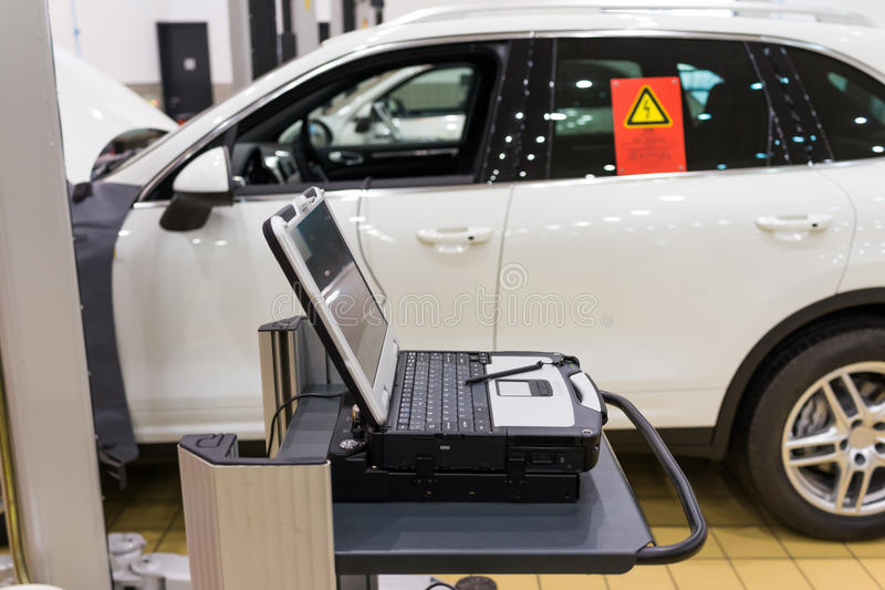 Car Repair Shop. Car in a professional auto repair shop,testing with laptop royalty free stock photo