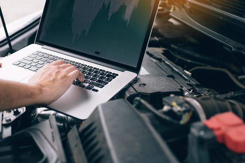 Car repair technicians use laptop computers to measure engine values for analysis.  stock image