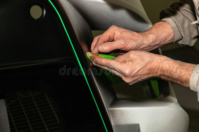 A car repair worker during work pastes with an green adhesive tape a part of the body element of white color in order not. A car repair worker during work pastes royalty free stock photography