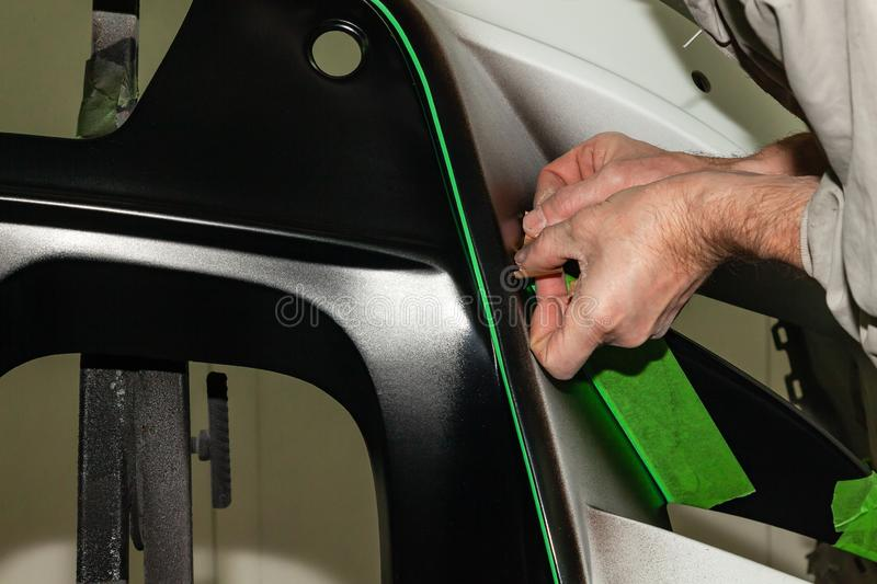 A car repair worker during work pastes with an green adhesive tape a part of the body element of white color in order not to fill. A car repair worker during royalty free stock image