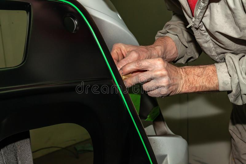 A car repair worker during work pastes with an green adhesive tape a part of the body element of white color in order not to fill. A car repair worker during royalty free stock photography