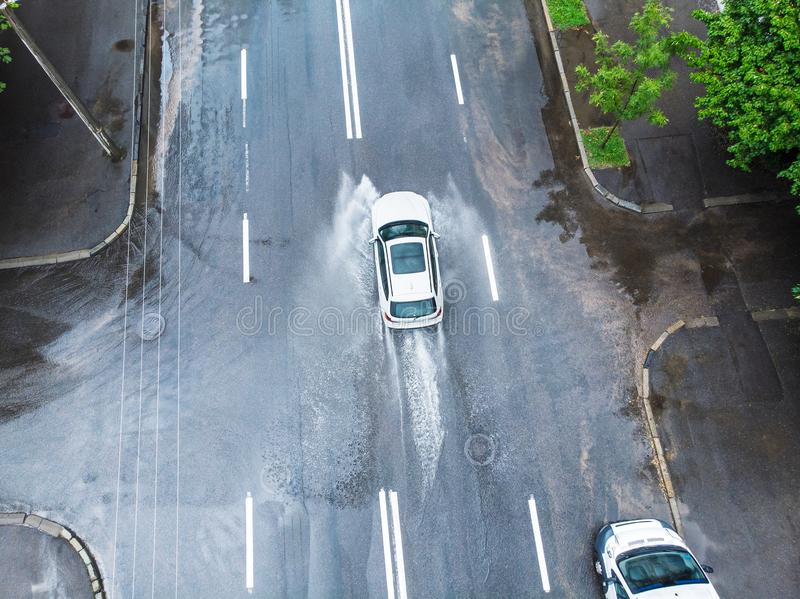 Car riding on wet road. rainwater spraying from car wheels. view. White car riding on wet road. rainwater spraying from car wheels. view from above stock images