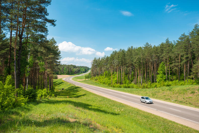 Car on road in forest. Belarus. Single car on country road in forest in Belarus. Blue sky with clouds in background. Beautiful and sunny summer or spring day stock photography