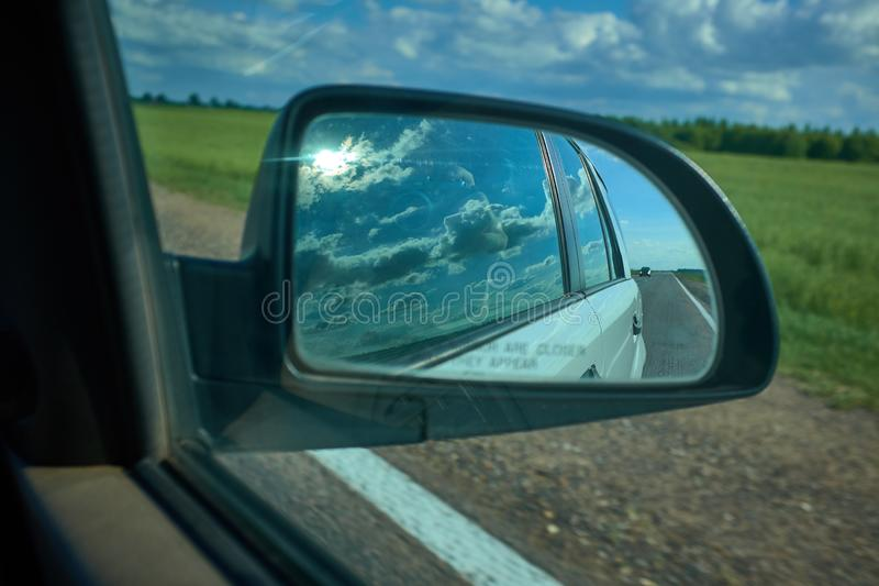 Car on the road with motion blur background and rear view mirror. Travel concept. Cloudy sky royalty free stock photo