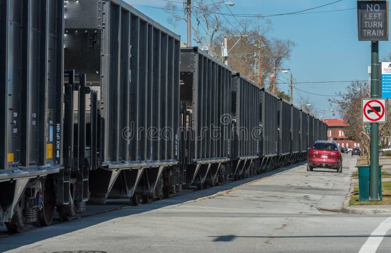 Car on road next to Coal Cars stock photos