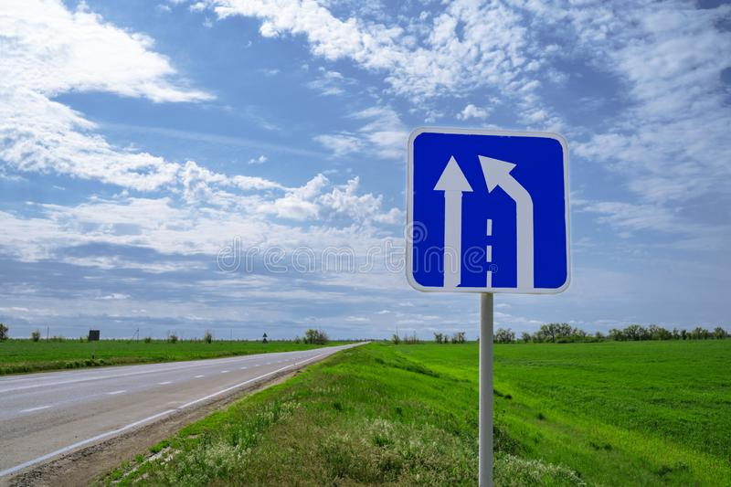 Car road sign `The end of the additional lane on the rise or runaway strip` against a blue sky.  stock image