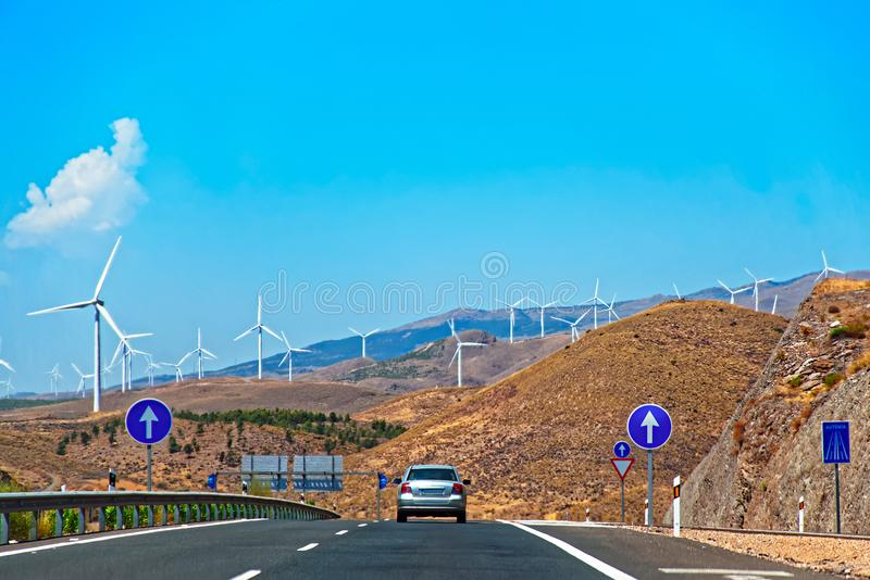 Car in road and wind turbines in Spain royalty free stock images