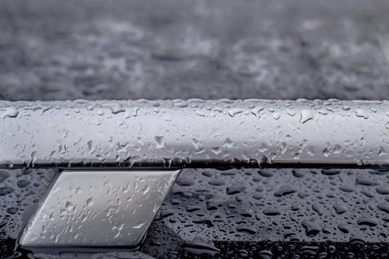 Car roof railing abstract closeup with rain drops, T letter shape. Alphabet stock images