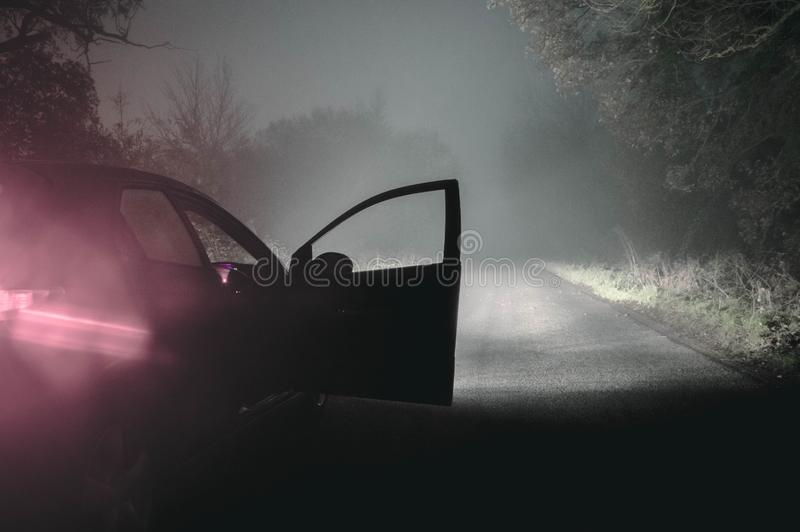 A car with it`s headlights on and door open on a spooky foggy wi royalty free stock photo