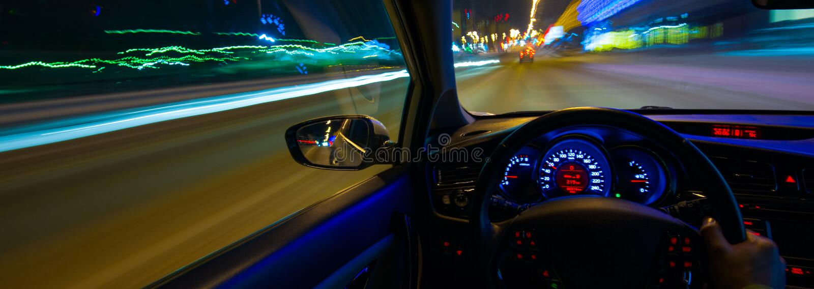 Movement of the car at night at a speed view from the interior, Brilliant road with lights with a car at high speed. The car`s movement at night with a kind of royalty free stock image