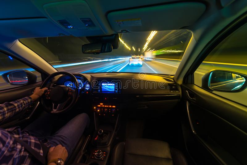 Movement of the car at night at a speed view from the interior, Brilliant road with lights with a car at high speed. The car`s movement at night with a kind of stock image