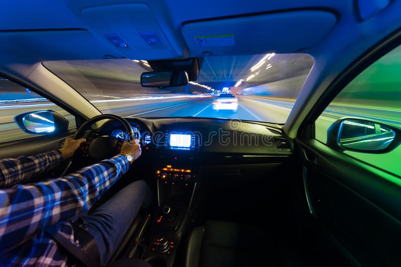 Movement of the car at night at a speed view from the interior, Brilliant road with lights with a car at high speed. The car`s movement at night with a kind of royalty free stock images