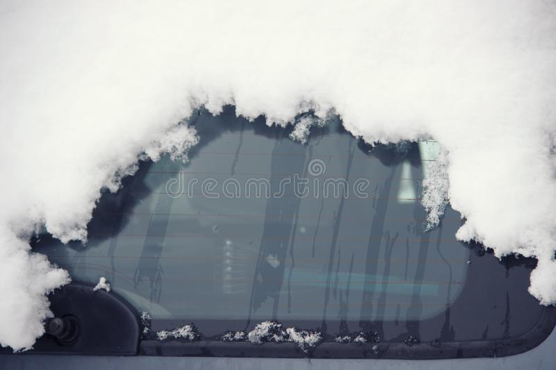 Car`s window covered up with snow in winter time, close up. Empty window for your message. Image has copy space for text.  royalty free stock photos
