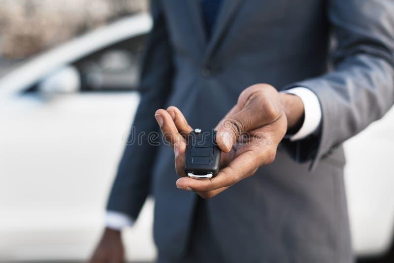 Car sale concept. Man hand giving car key. Car sale concept. Man in suit giving car key, focus on hand royalty free stock image
