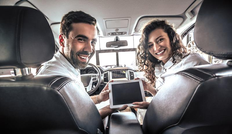 Close up view of couple sitting in a new car with tablet pc computer at auto show or salon from back royalty free stock photography