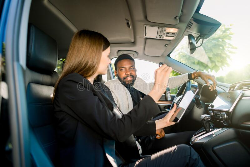 Car sale and rent, people concept. Happy African man and Caucasian woman car dealer with tablet computer sitting in new. Car sale and rent, people concept. Happy stock photography