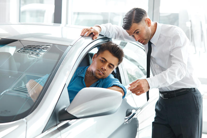 Car Sales Consultant Showing a New Car to a Potential Buyer in S royalty free stock photos