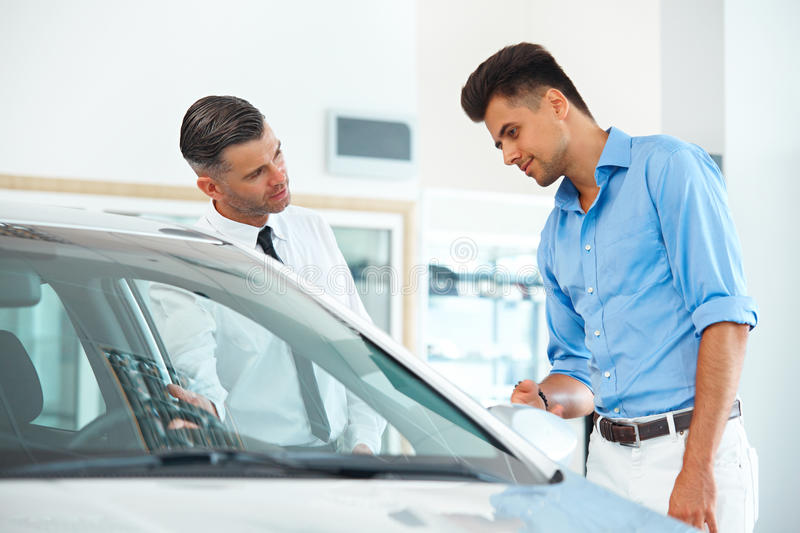 Car Sales Consultant Showing a New Car to a Potential Buyer in S stock image