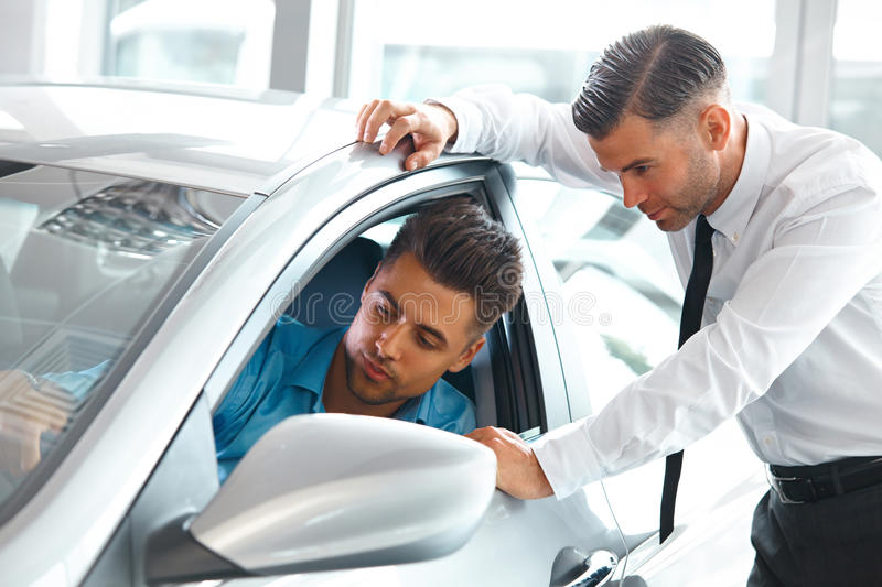 Car Sales Consultant Showing a New Car to a Potential Buyer in S stock images