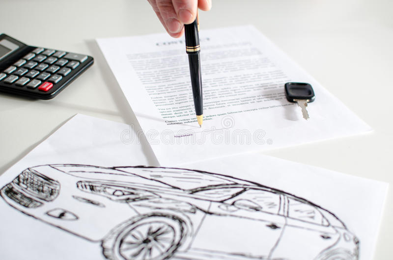 Car sales contract. Car salesman showing where to sign on a contract stock photos