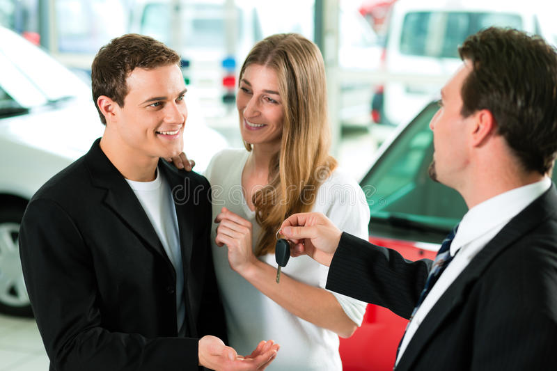 Car sales - key being given to couple royalty free stock image