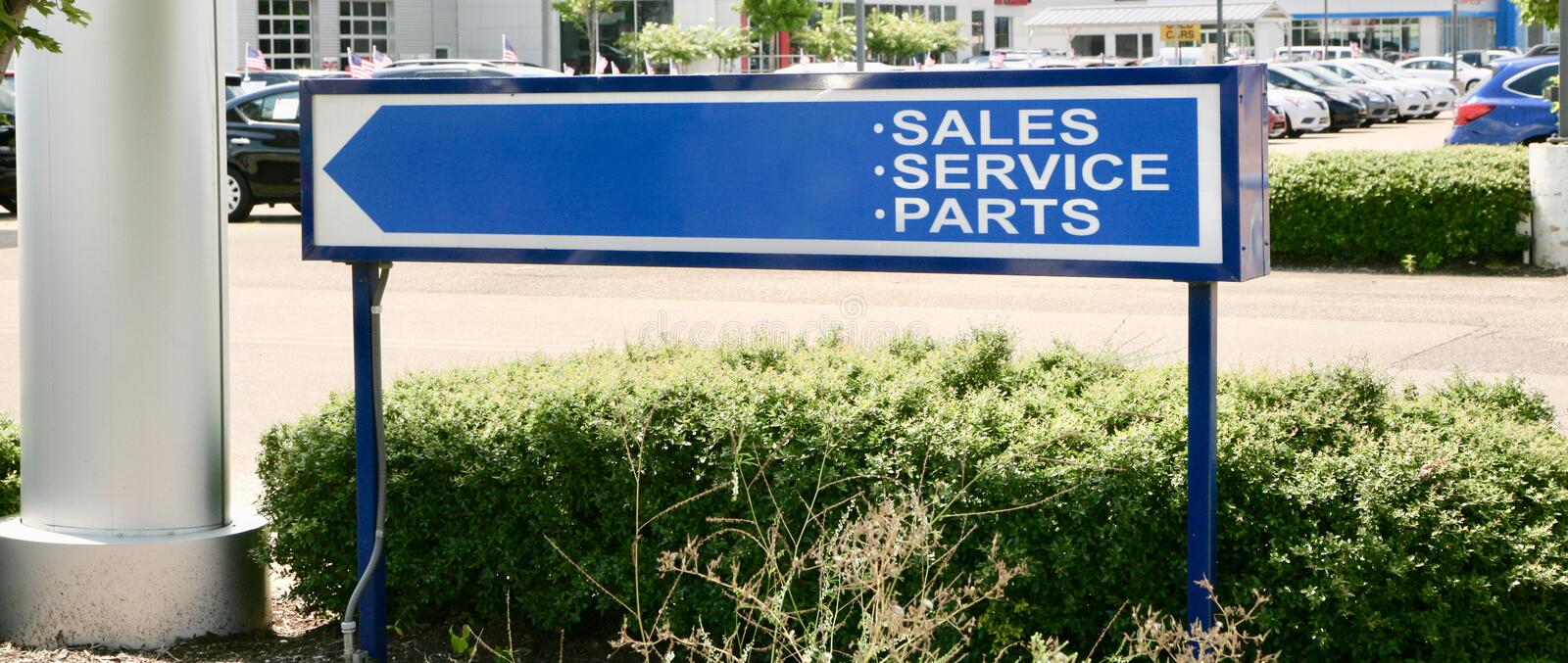 Car Sales, Service and Parts. A sign at a car dealership directs customers to a parts desk, automotive sales and the customer service desk stock photos
