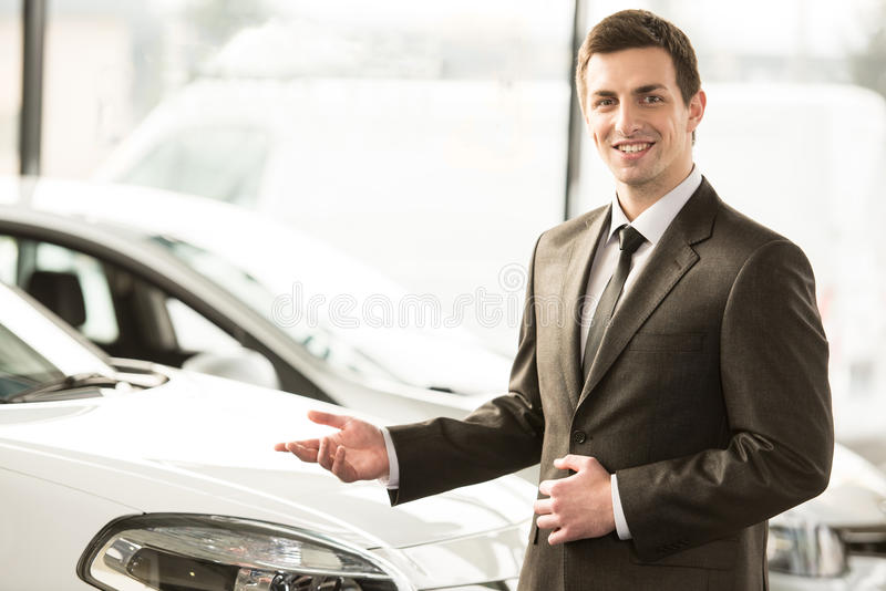 Car sales. Young man consultant in showroom is standing near car. Top view stock photos