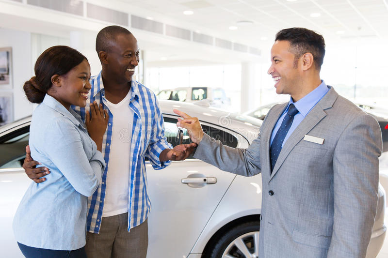 Car salesman couple. Mid age car salesman handing over new car key to african couple in car showroom stock photography