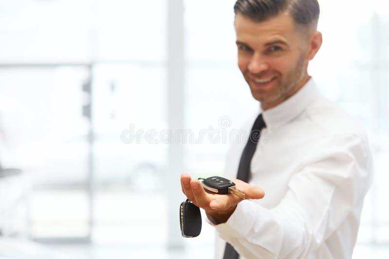 Car Salesman Giving Key of New Car at Showroom.  stock photography