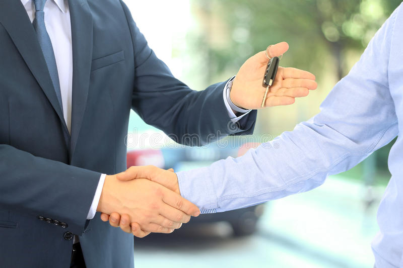 Car salesman handing over the keys for a new car to a young businessman . Handshake between two business people. Focus on a key.  stock photos