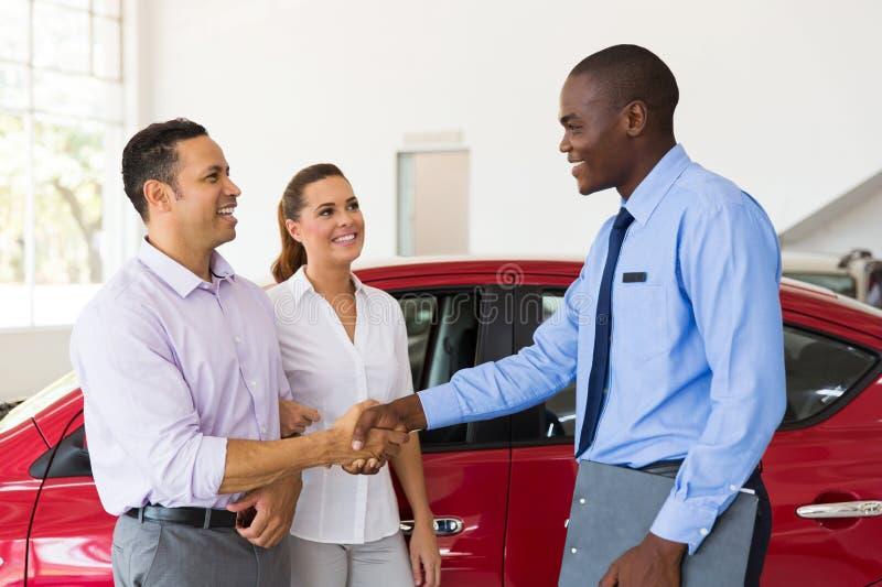 Car salesman handshaking buyer stock images