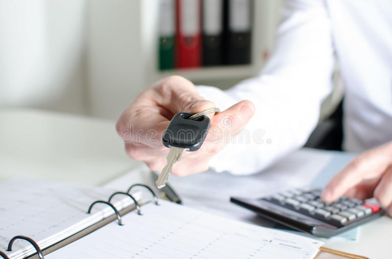Car salesman holding a key and calculating a price. At the dealership office stock image