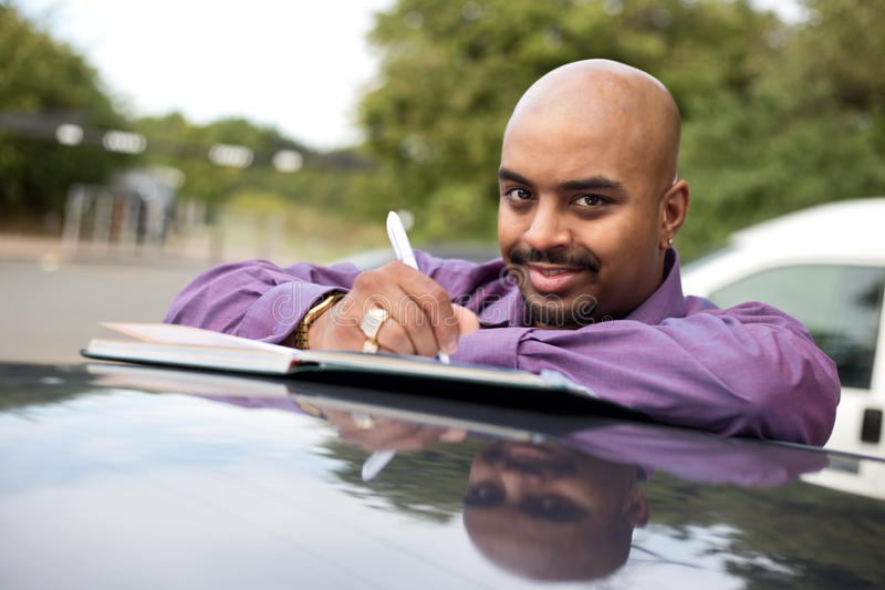 Car salesman. Man writing in a notebook on top of his car royalty free stock image