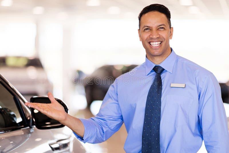 Car salesman presenting. Good looking mid age car salesman presenting new cars stock photo