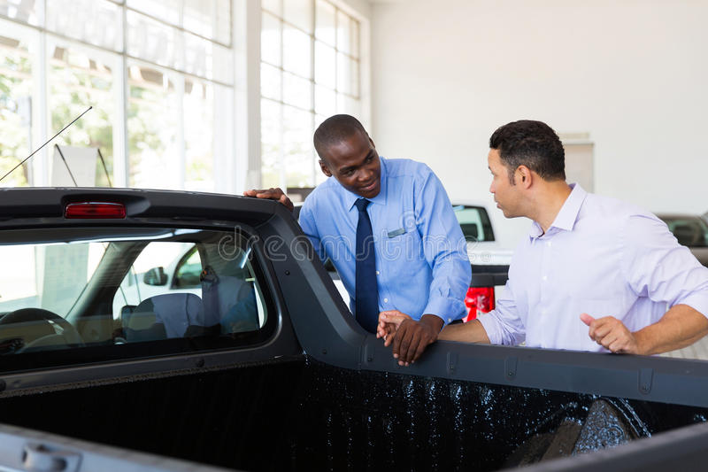 Car salesman selling. Confident car salesman selling a car to middle aged customer stock images
