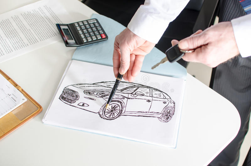 Car salesman showing a car design. At the dealership office royalty free stock photo