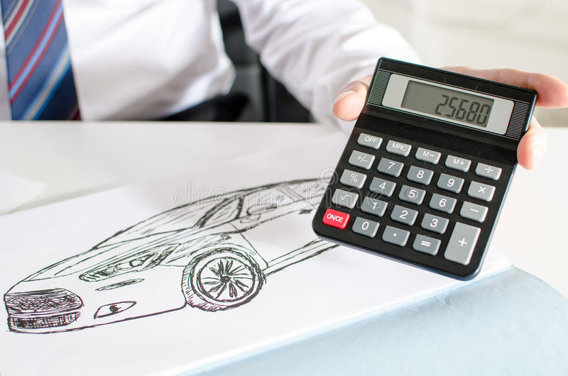 Car salesman showing the price of a car. At the dealership office royalty free stock image
