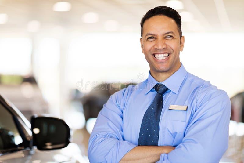 Car salesman in showroom. Cheerful car salesman standing in showroom royalty free stock photo