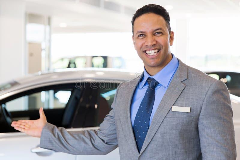 Car salesman welcoming. Friendly car salesman welcoming gesture at car dealership royalty free stock photos