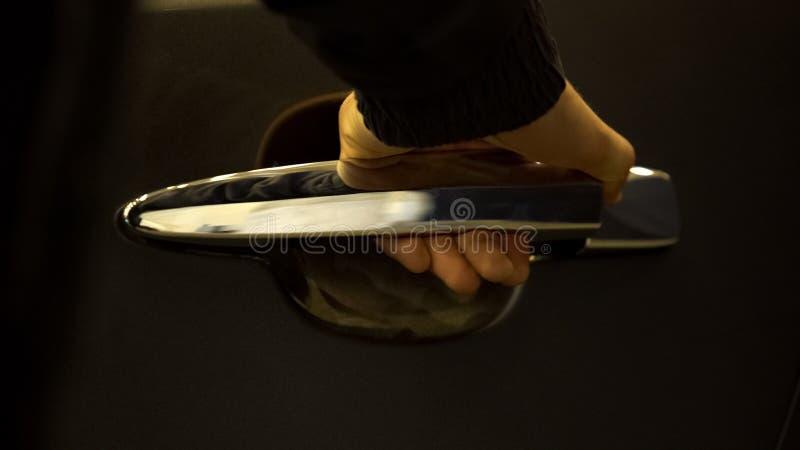 Car salon worker opening luxury automobile door closeup, vehicle exhibition stock images