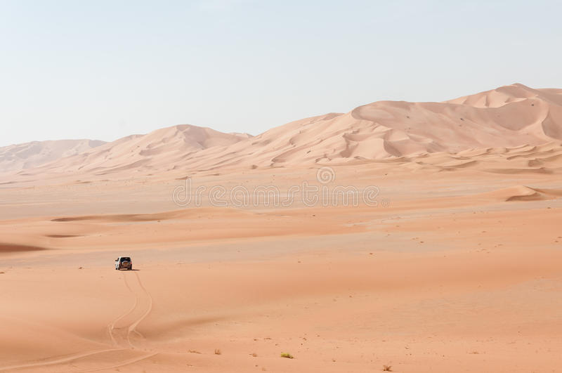Car among sand dunes in Oman desert (Oman). Car among sand dunes in Rub al-Khali desert at sunset, Dhofar region (Oman royalty free stock photo