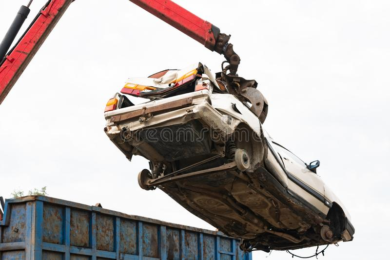 Car in a scrap yard being lifted by a mechanical grabber crane to be scrapped stock image